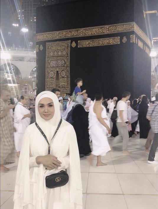 Yuni Shara berpose di depan Kabah mengenakan pakaian ihram. Untuk membawa perlengkapannya, ia mengenakan tas Gucci belt seharga sekitar Rp16 jutaan. (Dok. yunishara36)