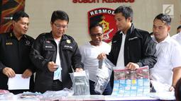 Petugas menunjukkan barang bukti pembobol uang dari mesin ATM dengan teknik skimming diperlihatkan petugas Resmob Polda Metro Jaya saat rilis di Jakarta, Sabtu (17/3). Kasus melibatkan empat WNA dan seorang WNI. (Liputan6.com/Helmi Fithriansyah)