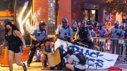 Polisi menyemprot demonstran dengan merica saat unjuk rasa atas kematian George Floyd oleh polisi di luar Third Police Precinct, Minneapolis, Minnesota, Amerika Serikat, Rabu (27/5/2020). Ribuan warga kulit hitam turun ke jalan menuntut polisi mengusut tuntas kasus tersebut. (Kerem Yucel/AFP)