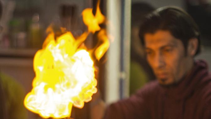 Api terlihat menyala di rambut seorang pelanggan di sebuah barbershop milik pria Palestina, Ramadan Edwan, di kamp pengungsian Rafah, di selatan Jalur Gaza, Rabu (1/2). Ramadan Edwan menggunakan api untuk mencukur rambut pelanggannya. (MAHMUD HAMS/AFP)