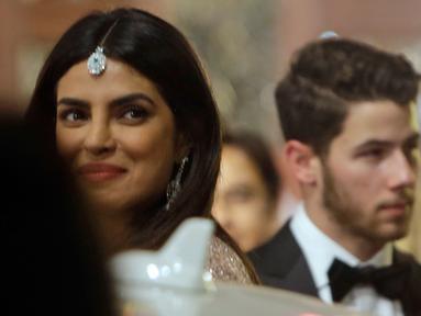 Aktris Bollywood, Priyanka Chopra dan suaminya yang juga musisi AS, Nick Jonas menghadiri pernikahan Isha Ambani dan Anand Piramal di Mumbai, Rabu (12/12). Isha merupakan putri orang terkaya di India menurut Forbes, Mukesh Ambani. (AP/Rajanish Kakade)