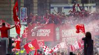 Para pemain Liverpool menyapa fans saat parade juara Liga Champions 2019 di Liverpool, Minggu (2/6). Ribuan fans tumpah ruah di jalanan untuk merayakan keberhasilan pemain membawa pulang trofi Si Kuping Besar ke kota Liverpool. (AP/Richard Sellers)