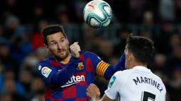 Striker Barcelona, Lionel Messi melompat saat berebut bola dengan pemain Granada, Jose Antonio Martinez pada lanjutan pertandingan La Liga Spanyol di Camp Nou, Minggu (19/1/2020). Messi tampil menjadi pahlawan kemenangan Barcelona yang mencetak satu-satunya gol di laga tersebut. (AP/Joan Monfort)
