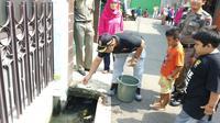 Warga Duren Sawit, Jakarta Timur lepas ratusan ikan kecil di selokan demi cegah demam berdarah. (Liputan6.com/Nanda Perdana Putra)
