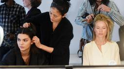Penata rias mempersiapkan Kendall Jenner, sebelum tampil dalam Michael Kors Autumn/Winter 2017 dalam acara New York Fashion Week di Manhattan, AS (15/2). (Jamie McCarthy / Getty Images untuk Michael Kors / AFP)