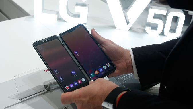 Pengunjung memeriksa smartphone LG V50 ThinQ 5G dalam gelaran Mobile World Congress (MWC) 2019 di Barcelona, Spanyol, Rabu (27/2). Perusahaan fokus pada layar yang dapat dilipat dan pengenalan jaringan nirkabel 5G.(Pau Barrena/AFP)