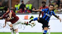 Striker Inter Milan, Lautaro Martinez, berebut bola dengan gelandang AC Milan, Hakan Calhanoglu, pada laga Serie A di Stadion San Siro, Milan, Sabtu (21/9). Milan kalah 0-2 dari Inter. (AFP/Miguel Medina)