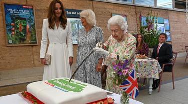 Ratu Elizabeth II memotong kue menggunakan pedang (AFP)