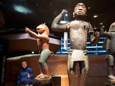 Pengunjung melihat sejumlah patung Kerajaan Dahomey di Museum Quai Branly, Paris, Prancis, Jumat (23/11). (AP Photo/Michel Euler)
