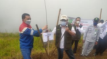Area Manager PGE Karaha Andi Joko Nugroho menyerahkan bibit pohon ganitri kepada Kepala Dinas Kehutanan Provinsi Jawa Barat Epi Kustiawan, saat pelaksanaan penghijauan di area lahan kritis Kawah Karaha, Tasikmalaya.