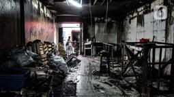 Pekerja membersihkan puing-puing buku yang terbakar di Toko Buku Setia Kawan, Senen, Jakarta, Rabu (14/10/2020). Pembakaran bekas gedung bioskop di kawasan Senen pada Kamis (8/10) oleh massa yang menolak UU Cipta Kerja juga berdampak pada ruko dan kios buku di sekitarnya. (merdeka.com/Iqbal Nugroho)