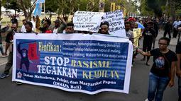 Ikatan Mahasiswa Pelajar dan Masyarakat Papua (IMMAPA) membawa spanduk saat berunjuk rasa di Lapangan Niti Mandala, Denpasar, Bali, Kamis (22/8/2019). Massa bawa spanduk bertulis 'Kami Bukan Monyet Kami Manusia Stop Rasis' hingga 'Stop Rasisme!! Kami Orang Papua Bukan Monyet'. (SONNY TUMBELAKA/AFP)