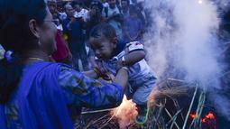 Seorang ibu mengasapi anaknya di sisa pembakaran patung iblis Ghantakarna selama Ghantakarna di kota kuno Bhaktapur, Nepal (30/7/2019). Ritual ini untuk merayakan kekalahan iblis dalam mitos Ghantakarna yang menyimbolkan penghancuran kejahatan. (AFP Photo/Prakash Mathema)