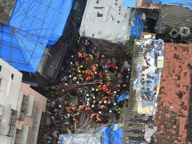 Petugas pemadam kebakaran India mencari korban setelah sebuah bangunan ambruk di Mumbai (16/7/2019). Dua orang tewas dan sedikitnya 40 terperangkap di bawah puing-puing setelah bangunan ambruk ketika hujan lebat. (AFP Photo/Punit Paranjpe)