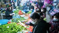 Orang-orang berbelanja sayuran di sebuah pasar di Wuhan, Provinsi Hubei, China, Kamis (23/1/2020). Pemerintah China mengisolasi Kota Wuhan yang berpenduduk sekitar 11 juta jiwa untuk menahan penyebaran virus corona. (Xiao Yijiu/Xinhua via AP)