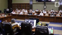 Menteri Ketenagakerjaan Ida Fauziah (tengah) rapat kerja dengan Komisi IX DPR di Kompleks Parlemen, Jakarta, Selasa (9/2/2021). Rapat membahas kesiapan penyelenggaraan program sistem penempatan satu kanal (SPSK) pekerja migran Indonesia (PMI) ke Arab Saudi. (Liputan6.com/Angga Yuniar)