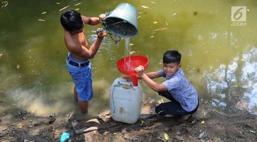 Dua anak Kampung Gamblok mengambil sisa air Kali Cihoe, Desa Ridomanah, Bekasi, Jawa Barat, Kamis (15/8/2019). Kemarau panjang sejak awal Ramadan memaksa warga mencari sisa air untuk diminum.