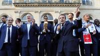 Presiden Emmanuel Macron menyampaikan sambutan di samping pelatih timnas Prancis, Didier Deschamps pada penyambutan tim sepakbola negaranya yang menjadi juara Piala Dunia 2018 di Istana Kepresidenan Elysee, Paris, Senin (16/7). (Ludovic Marin/Pool via AP)