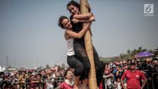 Warga negara asing mengikuti panjat pinang kolosal dalam rangka merayakan HUT ke-74 Kemerdekaan RI di Pantai Karnaval, Ancol, Jakarta, Senin (17/8/2019). Sebanyak 174 batang pinang dengan beragam hadiah disediakan dalam lomba yang diikuti ratusan warga itu. (Liputan6.com/Faizal Fanani)