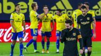 Striker Barcelona, Lionel Messi, tertunduk lesu usai ditaklukkan Cadiz pada laga Liga Spanyol di Stadion Ramon Carranza, Minggu (6/12/2020). Barcelona takluk dengan skor 1-2. (AP/Alvaro Rivero)