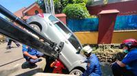 Petugas Damkar mengevakuasi mobil yang terpersok ke selokan di Jalan Pembaharuan, Kelapa Dua Wetan, Ciracas, Jakarta Timur. (Sudin Gulkarmat Jaktim)