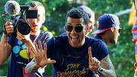 Ekspresi Dani Alves saat mengikuti pawai untuk merayakan gelar La Liga ke-24, Minggu (15/5/2016). (AFP/Pau Barrena)