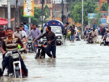 Para pengendara sepeda motor menuntun kendaraan mereka melewati banjir usai hujan monsun di Kota Karachi, Pakistan, 25 Agustus 2020. Menurut Departemen Meteorologi Pakistan, hujan monsun yang lebat pada Agustus ini memecahkan rekor sebagai curah hujan tertinggi dalam 36 tahun terakhir. (Xinhua/Str)