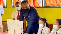 CEO PTPN V Jatmiko Santosa menjajal komputer dan internet yang merupakan bantuan pihaknya kepada sekolah daerah terpencil di Riau. (Liputan6.com/M Syukur)