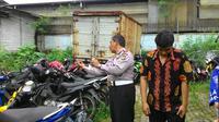 Pengemudi Fortuner yang menabrak sepeda motor dan menewaskan 4 orang, Riki Agung Prasetio (kanan), saat melihat kondisi motor korban. (Liputan6.com/Ahmad Romadoni)