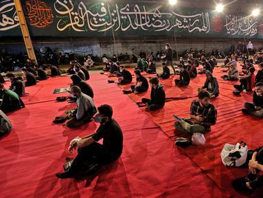 Warga Iran dengan mengenakan masker menghadiri acara kajian dan pengajian Lailatul Qadar, salah satu malam paling suci selama bulan Ramadan, di luar masjid di Teheran, Rabu (13/5/2020). Pemerintah Iran membuka kembali masjid-masjid untuk manyambut malam Lailatul Qadar. (ATTA KENARE/AFP)