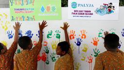 Siswa menempel tangan berlumuran cat air ke dinding di SD Negeri 15 Karet Tengsin, Jakarta, Rabu (18/10). Kegiatan ini digelar dalam rangka Hari Cuci Tangan Pakai Sabun Sedunia yang jatuh setiap tanggal 15 Oktober. (Liputan6.com/Fery Pradolo)