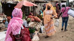 Mame Sey, istri Bara Tambedou, mengenakan masker saat ke pasar membeli makanan pada bulan suci Ramadan, di Dakar, Senegal, 25 April 2020. Tahun ini, banyak keluarga menjalankan Ramadan di rumah dengan larangan pertemuan publik dan jam malam untuk menekan penyebaran Covid-19. (AP/Sylvain Cherkaoui)