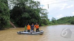 Petugas dari BNPB membantu warga menyeberangi sungai Ciberang dengan perahu karet di Lebak, Banten, Senin (16/3). Pasca robohnya jembatan gantung di atas Sungai Ciberang, warga terpaksa menyeberang mengunakan perahu karet. (Liputan6.com/Herman Zakharia)