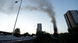 Pemandangan dari jauh gedung apartemen bertingkat 27 lantai yang terbakar di London (14/6). Pernyataan dari kepala pemadam kebakaran, api telah menjalar dari lantai dua hingga paling atas. (AP Photo/Matt Dunham)