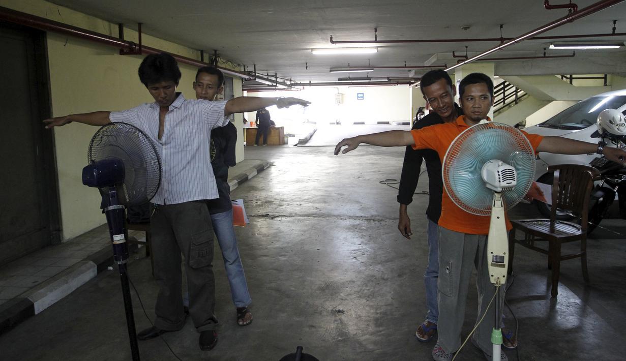 Calon pengemudi ojek online mengangkat kedua tangan mereka saat mengikuti tes bau badan di sebuah tempat parkir bawah tanah di Jakarta, 9 Januari 2016. Uji bau badan ini dilakukan demi meningkatkan kualitas pelayanan. (REUTERS/Garry Lotulung)