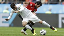 Gelandang Uruguay, Rodrigo Bentancur, berebut bola dengan striker Mesir, Marwan Mohsen, pada laga Piala Dunia di Stadion Ekaterinburg, Jumat (15/6/2018). Uruguay menang 1-0 atas Mesir. (AP/Natacha Pisarenko)