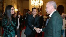 Presiden Turki Recep Tayyip Erdogan bersalaman dengan Gelandang Mesut Ozil saat acara buka puasa bersama di Istana Dolmabahce, Istanbul (19/5). Acara buka puasa ini turut mengundang generasi muda Turki menjelang perayaan Hari Pemuda dan Olahraga. (Stringer/Turkish President's Press Office/AFP)