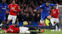 Gelandang Chelsea, Eden Hazard berusaha melewati bek MU, Eric Bailly saat bertanding pada lanjutan Liga Inggris di Stamford Bridge di London (5/11). Chelsea Menang tipis atas MU 1-0. (AP Photo/Kirsty Wigglesworth)