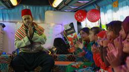 Anak-anak Suriah yang terlantar bernyanyi di sebuah bus yang diubah menjadi ruang kelas di dekat desa Hazano di Suriah barat laut (15/9/2019). Sejak proyek itu diluncurkan pada Mei, sekitar 1.000 anak telah mendapat manfaat dari program kelas bus ini. (AFP Photo/Aaref Watad)