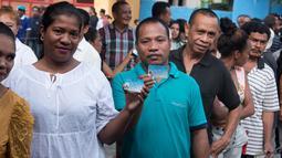 Warga Timor Leste menunjukkan kartu identitasnya saat mengantre untuk menggunakan hak pilih mereka di tempat pemungutan suara (TPS) di Dili, Senin (20/3). Sedikitnya 1,2 juta warga akan memilih presiden baru Timor Leste. (Valentino DARIEL SOUSA/AFP)