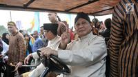Pasangan capres dan cawapres Prabowo Subianto-Sandiaga Uno menaiki mobil golf sambil menunjukkan salam dua jari saat mengikuti pawai Deklarasi Kampanye Damai di Monas, Minggu (23/9). (Merdeka.com/Iqbal Nugroho)