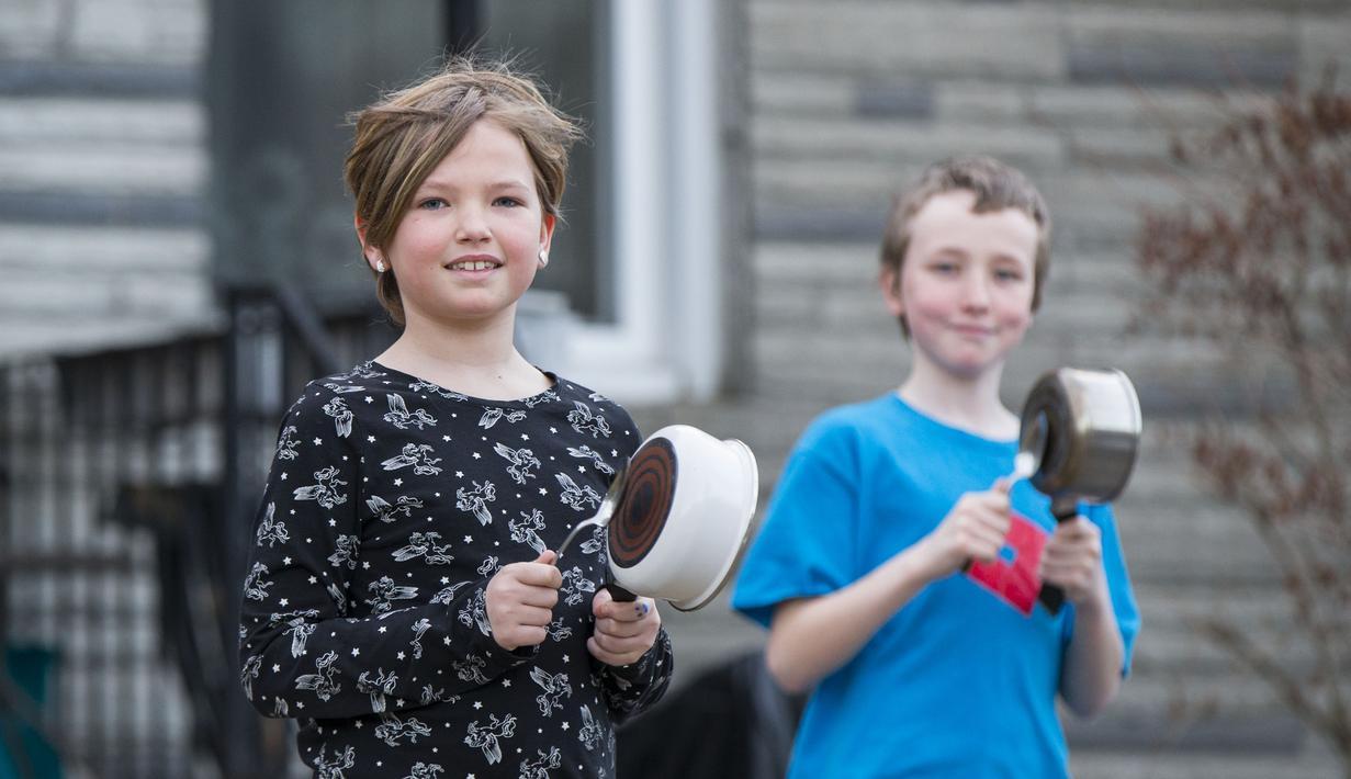 Anak-anak memukul panci saat menyemangati petugas medis memerangi virus corona COVID-19 di Toronto, Kanada, Minggu (29/3/2020). Aksi membuat bunyi-bunyian di luar rumah tersebut rutin dilakukan setiap sore. (Xinhua/Zou Zheng)