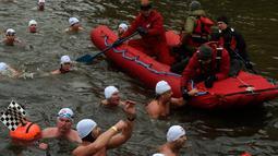 Orang-orang mengambil bagian dalam kompetisi berenang Natal tahunan di sungai Vltava, ibu kota Republik ceko, Praha, Rabu (26/12). Dalam menyemarakkan Natal, para peserta mengikuti lomba renang di sungai bersuhu dingin. (Michal CIZEK / AFP)