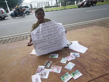 Nelly Hutabarat, guru asal Deli Serdang, Sumatera Utara, melakukan aksi diam di depan Istana Negara, Jakarta, Rabu (13/7). Nelly menuntut keadilan atas penutupan SDN 10-61-59 dan pembongkaran rumah dinasnya pada 2011 silam (Liputan6.com/Immanuel Antonius)