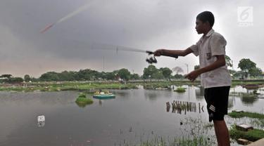 Seorang anak memancing di area banjir yang merendam TPU Semper, Jakarta, Selasa (4/12). TPU Semper menjadi langganan banjir saat musim penghujan akibat rendahnya permukaan tanah dengan ketinggian air sepinggang orang dewasa. (Merdeka.com/Iqbal S. Nugroho)