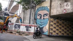 Pengendara motor melintas dekat lukisan mural melawan COVID-19 di Kawasan Cikokol, Cawang, Jakarta, Minggu (4/10/2020).  Mural masih dianggap menjadi sarana edukasi kesehatan yang tepat bagi warga untuk menjaga diri dari penularan virus Covid 19. (Liputan6.com/Faizal Fanani)