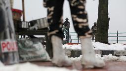 Tentara paramiliter India berjaga-jaga di jalan yang tertutup salju di Srinagar, Kashmir yang dikuasai India (7/1). Musim salju telah mengakibatkan gangguan lalu lintas udara dan lalu lintas jalan antara Srinagar dan Jammu. (AP Photo/Mukhtar Khan)
