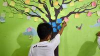 Seorang bocah tengah menempelkan kertas bertuliskan asa di pohon harapan. (Liputan6.com/Muhammad Ali)