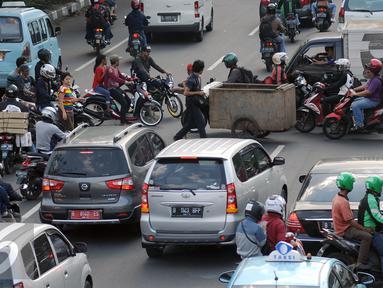 Suasana arus lalu lintas di sebuah persimpangan jalan Kramat Raya, Jakarta (22/6/2016). Pemprov DKI Jakarta harus membuat kebijakan atau terobosan radikal untuk segera mengatasi kemacetan di Jakarta. (Liputan6.com/Helmi Fithriansyah)