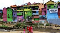 Suasana kampung warna-warni di Kelurahan Kesatrian, Kota Malang, Minggu (5/11). Ratusan rumah yang berdiri di bantaran Sungai Brantas di cat gambar warna-warni. (Liputan6.com/Fery Pradolo)